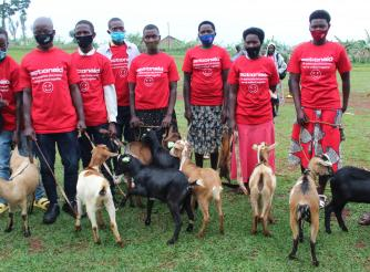 Graduates posing in a group photo holding AAR gift of goats
